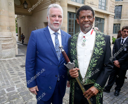 Haitian-born Canadian writer Dany Laferriere poses with Quebec Premier Philippe Couillard, left, after his induction ceremony at the Academie Francaise, French Academy, in Paris, . Dany Laferriere is a Haitian Canadian novelist and journalist who writes in French