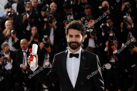 Stock Photo of Ely Dagher Waves '98 director Ely Dagher holds the Palme d'Or award for best short film as he poses for photographers during a photo call following the awards ceremony at the 68th international film festival, Cannes, southern France