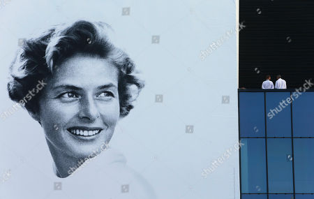 Two men stand on a terrace at the Palais des Festivals alongside the official festival poster depicting actress Ingrid Bergman, during the 68th international film festival, Cannes, southern France