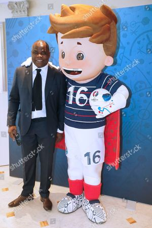 "Former Olympique Marseille defender Basile Boli, poses with mascot 'Super Victor "" at press conference to mark the one year to go before the start of EURO 2016 soccer tournament in Paris"