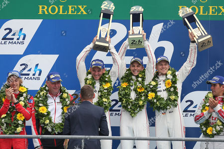 Nine time winner Tom Kristensen of Denmark gives the trophy to the Porsche 919 Hybrid No19 Team, from left, Earl Bamber of New Zealand, Nick Tandy of Great Britain and Nico Hulkenberg of Germany, during the podium ceremony of the 83rd 24-hour Le Mans endurance race, in Le Mans, western France