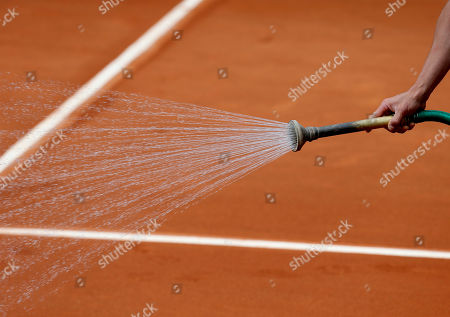 A stadium employee waters the court before Serbia's Jelena Jankovic plays Bulgaria's Sesil Karatantcheva during their first round match of the French Open tennis tournament at the Roland Garros stadium, in Paris