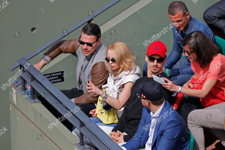 Swedish PSG striker Zlatan Ibrahimovic, center right with red cap, and his wife Helena Seger, second left, watch the second round match of the French Open tennis tournament between Serbia's Novak Djokovic and Luxembourg's Gilles Muller at the Roland Garros stadium, in Paris, France