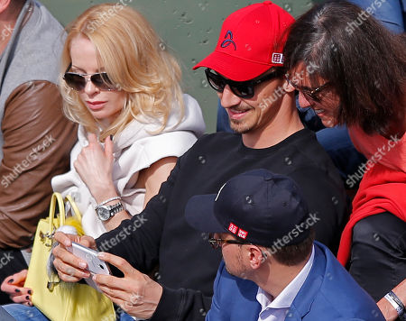 Swedish PSG striker Zlatan Ibrahimovic, center right with red cap, takes a selfie with the phone of a fan, right, as he watches the second round match of the French Open tennis tournament between Serbia's Novak Djokovic and Luxembourg's Gilles Muller at the Roland Garros stadium, in Paris, France, . Left is Ibrahimovic's wife Helena Seger