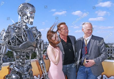 From right, British actress Emilia Clarke, Austrian born actor Arnold Schwarzenegger, center, and US director Alan Taylor, pose for photographers at a preview of the film, 'Terminator: Genisys', in front of Arch of Triumph, in Paris, France