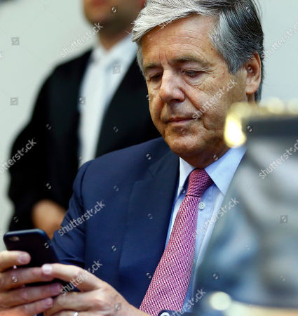 Former Deutsche Bank CEO Josef Ackermann checks his cell phone after arriving in a court room in Munich, Germany, where he and former top managers of Deutsche Bank face trial on accusations of giving false statements in the proceedings of the bankruptcy of German Kirch media group
