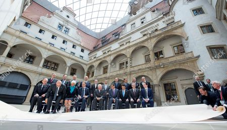 Workers remove a white carpet in front of Pier Carlo Padoan, Finance Minister of Italy, Michel Sapin, Finance Minister of France, Christine Lagarde, Managing Director of International Monetary Fund, IWF, Jens Weidmann, president of the German Central Bank, German Finance Minister Wolfgang Schaeuble, Jacob J. Lew, US Secretary of the Treasury, Japanese Finance Minister Taro Aso, Joe Oliver, Finance Minister of Canada, British Chancellor of the Exchequer George Osborne, first row from left to right, Ignazio Visco, Governor of the Banca d'Italia, Mario Draghi, President of the European Central Bank, Stephen S. Poloz, Governor of the Bank of Canada, Pierre Moscovici, EU Commissioner for Economic and Financial Affairs, Taxation and Customs, Steve B. Kamin, director of the Division of International Finance, Haruhiko Kuroda, Governor of the Bank of Japan, Jim Yong Kim, President of the World Bank Group, Bank of England's Governor Mark Carney, Christian Noyer, Governor of the Banque de France, and Jose Angel Gurria, OECD Secretary General, second row from left to right, after a group photo session during the G7 Finance Ministers meeting at the Dresden Castle in Dresden, eastern Germany, . The G7 Finance Ministers meeting is being held in Dresden from May 27 to May 29, 2015