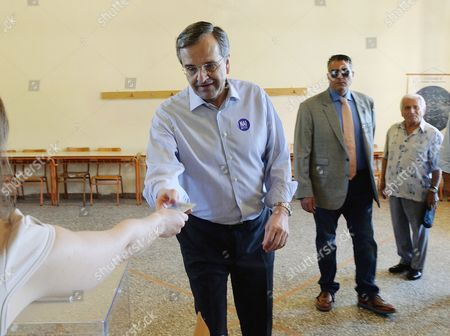 Antonis Samaras Former Greek Prime Minister and conservative opposition leader Antonis Samaras shows his ID as he prepares to vote at a polling station in the town of Pylos, southwestern Greece, . Greeks were voting Sunday in a bailout referendum that will decide the country's future, with opinion polls showing people evenly split on whether to accept creditors' proposals for more austerity in exchange for rescue loans or defiantly reject the deal