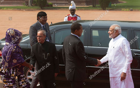 Stock Photo of Indian Prime Minister Narendra Modi, right, welcomes Tanzanian President Jakaya Kikwete as Indian President Pranab Mukherjee, second left, shakes hand with Tanzanian President's wife Salma Kikwete at the Indian presidential palace, in New Delhi, India, . President Kikwete is on a five day official visit to India