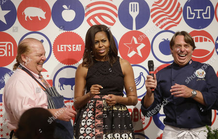 U.S. first lady Michelle Obama shares a light moment with cooks Mario Batali, left, and John Besh, during a cooking demonstration at the James Beard American Restaurant with Italian and American middle school students in Milan, Italy, . Michelle Obama is in Milan on the second leg of a European trip that puts an international spin on her core initiatives