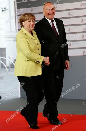 German Chancellor Angela Merkel, left, is greeted by Latvian President Andris Berzins as she arrives for a formal dinner at the Eastern Partnership summit in Riga, on . EU leaders on Thursday will seek new ways to bolster ties with six post-communist nations in Eastern Europe, a year and a half after a previous summit of the Eastern Partnership ended with a fateful standoff over Ukraine