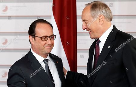 French President Francois Hollande, left, speaks with Latvian President Andris Berzins as he arrives for a formal dinner at the Eastern Partnership summit in Riga, on . EU leaders on Thursday will seek new ways to bolster ties with six post-communist nations in Eastern Europe, a year and a half after a previous summit of the Eastern Partnership ended with a fateful standoff over Ukraine