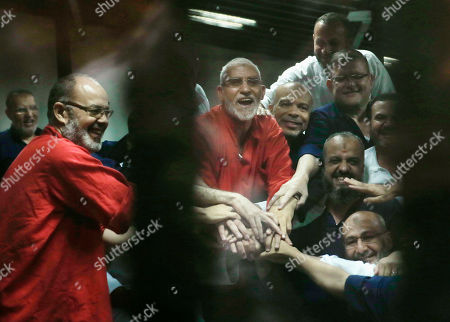 Mohammed Badie Egyptian defendants including the spiritual leader of the Muslim Brotherhood, Mohammed Badie, center in orange, react to a court ruling in a makeshift courtroom at the Police Academy courthouse in Cairo, Egypt, . An Egyptian court confirmed death sentences handed to ousted Islamist President Mohammed Morsi over a mass prison break during the 2011 uprising that eventually brought him to power and five other leading members including Badie