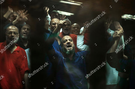 Stock Photo of Mohammed el-Beltagy, Essam el-Erian, Khairat el-Shater Senior Muslim Brotherhood leading members including Mohammed el-Beltagy, center, make a four-fingered gesture referring to the 2013 killing of Muslim Brotherhood protesters at the Rabaah Al-Adawiya mosque, in a makeshift courtroom at the Police Academy courthouse in Cairo, Egypt, . An Egyptian court confirmed death sentences handed to ousted Islamist President Mohammed Morsi over a mass prison break during the 2011 uprising that eventually brought him to power. The court also confirmed a death sentence for el-Beltagy over charges of conspiring with foreign groups