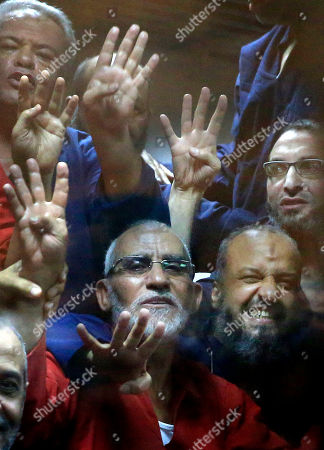 Mohammed Badie, Mohammed el-Beltagy Egyptian defendants including the spiritual leader of the Muslim Brotherhood, Mohammed Badie, bottom left, and Senior Muslim Brotherhood leader Mohammed el-Beltagy, right, make a four-fingered gesture referring to the 2013 killing of Muslim Brotherhood protesters at the Rabaah Al-Adawiya mosque, in a makeshift courtroom at the Police Academy courthouse in Cairo, Egypt, . An Egyptian court on Tuesday confirmed a death sentence handed to ousted Egyptian President Mohammed Morsi over a mass prison break during the 2011 uprising that eventually brought him to power. The judge also confirmed death sentences for five other jailed leading members of Morsi's Muslim Brotherhood, including Badie, the group's leader, and Saad el-Katatni, the head of its short-lived political party