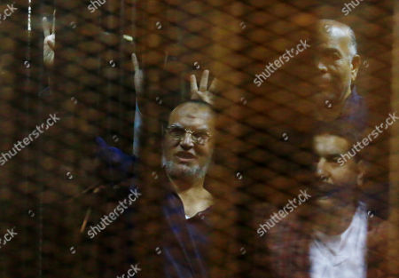 Stock Photo of Essam el-Erian Egyptian defendants including the Senior Muslim brotherhood leader Essam el-Erian, center, make a four-fingered gesture referring to the 2013 killing of Muslim Brotherhood protesters at the Rabaah Al-Adawiya mosque, in a makeshift courtroom at the Police Academy courthouse in Cairo, Egypt, . An Egyptian court confirmed death sentences handed to ousted Islamist President Mohammed Morsi over a mass prison break during the 2011 uprising that eventually brought him to power and five other leading members including el-Erian