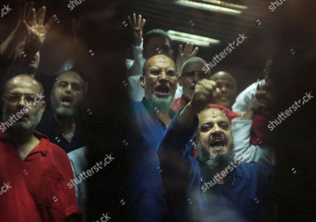 Stock Picture of Mohammed el-Beltagy, Essam el-Erian, Khairat el-Shater Senior Muslim Brotherhood leader Mohammed el-Beltagy, right, Senior Muslim brotherhood leader Essam el-Erian, second right, Muslim Brotherhood nominated deputy leader Khairat el-Shater, second left, make a four-fingered gesture referring to the 2013 killing of Muslim Brotherhood protesters at the Rabaah Al-Adawiya mosque, in a makeshift courtroom at the Police Academy courthouse in Cairo, Egypt, . An Egyptian court on Tuesday confirmed a death sentence handed to ousted Egyptian President Mohammed Morsi over a mass prison break during the 2011 uprising that eventually brought him to power. The judge also confirmed death sentences for five other jailed leading members of Morsi's Muslim Brotherhood, including Mohammed Badie, the group's leader, and Saad el-Katatni, the head of its short-lived political party