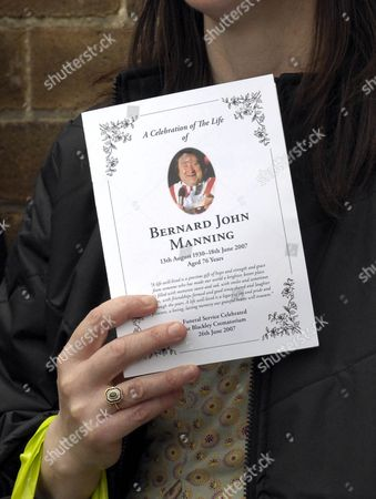 A woman holds a copy of the order of service at the funeral of comedian Bernard Manning