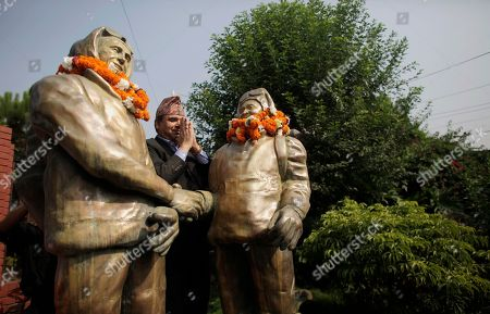 A man garlands the statues of New Zealander Edmund Hillary, left, and his Sherpa guide Tenzing Norgay, who became the first climbers to reach the top of 8,850-meter (29,035-foot) Everest on May 29, 1953, in Kathmandu, Nepal, . Everest Day, marking the conquest of the world's tallest peak 62 years ago, was marked quietly by officials, people in the mountaineering business and a few climbers Friday, little more than a month after an earthquake-triggered avalanche swept the base camp and killed 19 people
