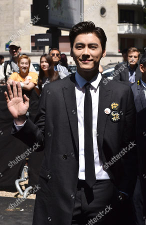 Chinese actor Li Yifeng waves as he arrives for the presentation of Dior Homme men's Spring-Summer 2016 fashion collection, in Paris, France