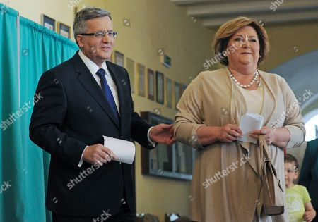 Bronislaw Komorowski, Anna Komorowska Polish President Bronislaw Komorowski and wife Anna hold their ballots as they vote during the presidential runoff election at a polling station in Warsaw, Poland, . Poles were voting Sunday in the final round of a cliffhanger presidential election race between the conservative incumbent Bronislaw Komorowski and an even more conservative challenger Andrzej Duda from the Law and Justice party