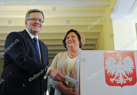 Bronislaw Komorowski, Anna Komorowska Polish President Bronislaw Komorowski casts his ballot as wife Anna looks, during the presidential runoff election at a polling station in Warsaw, Poland, . Poles were voting Sunday in the final round of a cliffhanger presidential election race between the conservative incumbent Bronislaw Komorowski and an even more conservative challenger Andrzej Duda from the Law and Justice party