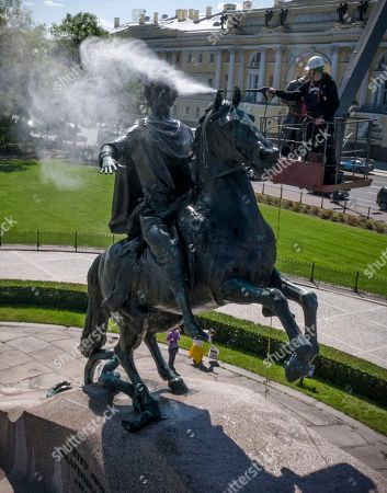 A worker washes a city landmarks, the equestrian statue of Peter the Great known as the Bronze Horseman by French sculptor Etienne Maurice Falconet, in St. Petersburg, Russia