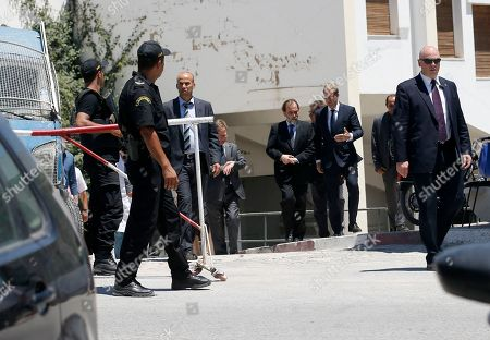 Tunisia's health minister Said Aidi, center left, and British Minister for North Africa Tobias Ellwood, center right, leave from morgue with bodies of several tourists in a local hospital in Tunis, Tunisia, . Thirty-eight tourists died in a gun attack just days before Tunisia planned to implement heightened security measures for the Muslim fasting month of Ramadan, but those plans had not anticipated an assault on tourist beaches, the country's president said Tuesday