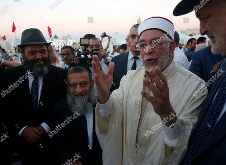 Abdelfattah Mourou, deputy chief of Tunisian Islamist movement Ennahda, right, welcomes Tunisia's Chief Rabbi, Haim Bitan, center before breaking their fast at the main square in the capital Tunis, Tunisia, . Government minister Kamel Jendoubi told reporters Thursday that eight people who are still being detained - seven men and one woman - are suspected of direct links to an attack which took place last week in Sousse