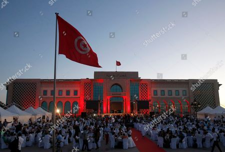 People break the fast at the main square in the capital Tunis, Tunisia, . Government minister Kamel Jendoubi told reporters Thursday that eight people who are still being detained - seven men and one woman - are suspected of direct links to an attack which took place last week in Sousse