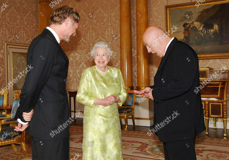 Poet Laureate, Professor Andrew Motion looks on as Queen Elizabeth II presents The Queen's Gold Medal for Poetry to James Fenton, right