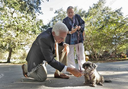 """Charlie Crist, Velva Lee Heraty Former Florida Gov. Charlie Crist reaches down to pet """"Miss Nena"""" as her owner Velva Lee Heraty looks on during an early voting kickoff party, at Williams Park in St. Petersburg, Fla. Crist is a democratic candidate for the U.S. Congress"""