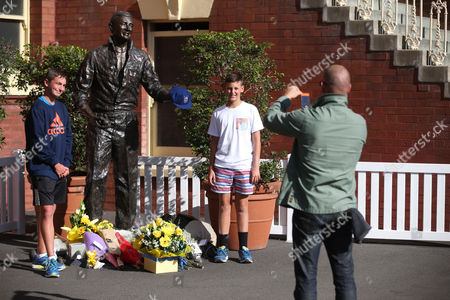Ian Coker, right, photographs his son Ben Coker, left, and his friend Finnian Murray next to a statue of former Australia cricket captain Richie Benaud at the Sydney Cricket Ground following the death of Benaud in Sydney, . Benaud played 63 tests for Australia, making his debut against the West Indies in 1952 and culminating in 1964 against South Africa, a transformative period in the game