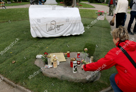A woman lays a rose in front of the grave stone for Austrian musician and Eurovision Song Contest winner Udo Juergens at the main Cemetery in Vienna, Austria, . Juergens died on Dec. 21, 2014 at the age of 80. The marble grave stone depicts a covered piano