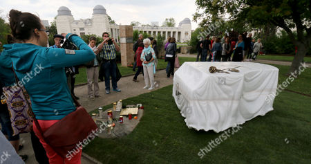 People visit the grave for Austrian musician and Eurovision Song Contest winner Udo Juergens at the main Cemetery in Vienna, Austria, . Juergens died on Dec. 21, 2014 at the age of 80. The marble grave stone depicts a covered piano