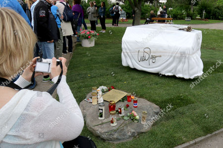 A visitor takes a photo of the grave stone for Austrian musician and Eurovision Song Contest winner Udo Juergens at the main Cemetery in Vienna, Austria, . Juergens died on Dec. 21, 2014 at the age of 80. The marble grave stone depicts a covered piano