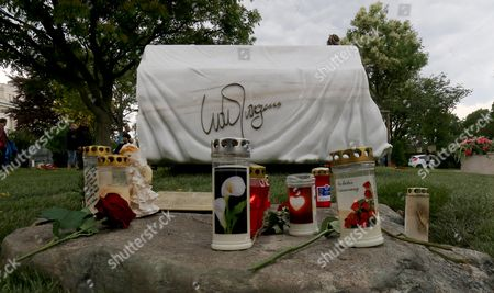 Candles and roses are placed in front of the grave stone for Austrian musician and Eurovision Song Contest winner Udo Juergens at the main Cemetery in Vienna, Austria, . Juergens died on Dec. 21, 2014 at the age of 80. The marble grave stone depicts a covered piano