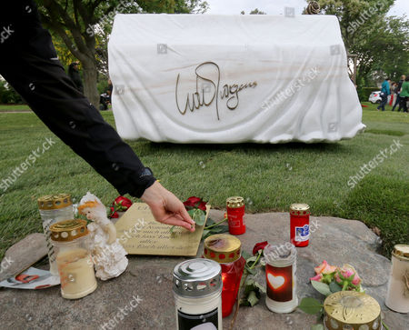 A person lays a rose in front of the grave stone for Austrian musician and Eurovision Song Contest winner Udo Juergens at the main Cemetery in Vienna, Austria, . Juergens died on Dec. 21, 2014 at the age of 80. The marble grave stone depicts a covered piano