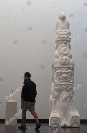 """A man walks past a Native American inspired totum pole made out of Styrofoam using the same techniques used for the floats in Rio's Carnival parades, at an exhibit designed by Mexican artist Damian Ortega and titled """"End of Matter"""" at the Modern Art Museum in Rio de Janeiro, Brazil. """"It's an homage to work, to the creative process,"""" said artist Damian Ortega, one of Mexico's best-known contemporary artists. Ortega got the idea for the show when he lived in Rio from 2012-2013 and encountered a larger-than-life-sized bull head of Styrofoam abandoned on the train tracks"""