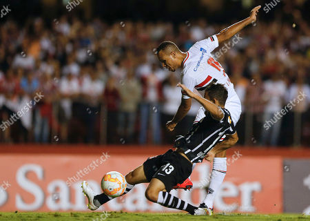 Luis Fabiano, Uendel Luis Fabiano of Brazil's Sao Paulo FC shoots to score his team's first goal as Uendel of Brazil's Corinthians, front, challenges him, during a Copa Libertadores soccer match in Sao Paulo, Brazil