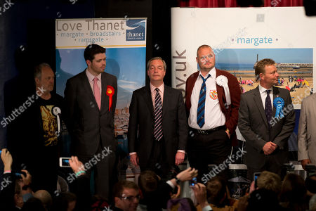 """Stock Picture of Nigel Farage, center, the leader of the UK Independence Party (UKIP) stands on stage as the results are announced for the count for the South Thanet seat won by the Conservative Party's Craig Mackinlay, right, stood next to, from left, We Are The Reality Party's Nigel Askew, the Labour Party's Will Scobie, and Al Murray a comedian who performs as """"The Pub Landlord""""at the Winter Gardens in Margate, south east England, . The Conservative Party swept to power Friday in Britain's Parliamentary elections, winning an unexpected and resounding victory that returns Prime Minister David Cameron to 10 Downing Street in a stronger position than before"""