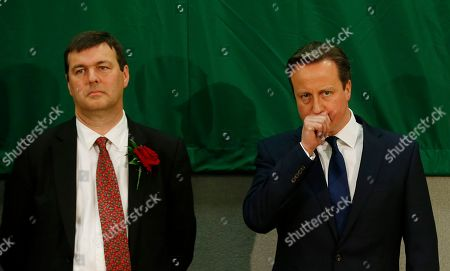 Britain's Conservative party leader David Cameron, right, coughs as he stands next to the Labour Party candidate Duncan Enright at his Witney constituency count in Witney, England, . Cameron won the seat and has been re-elected as lawmaker for Witney