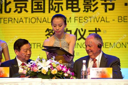 Li Shilin, Dick Cook A hostess hands agreements to Li Shilin, left, head of China's CITIC Guoan, a unit of state-owned CITIC Group Corporation, and Dick Cook, former Walt Disney Studios Chairman and current head of Dick Cook Studios, as they sign an agreement during a contract signing event held as part of the Beijing International Film Festival in Beijing, . Chinese and foreign film producers, companies and investment firms signed movie cooperation deals worth 13.8 billion RMB ($2.3 billion) on Monday, demonstrating how foreign movie makers increasingly want a piece of the growing Chinese market