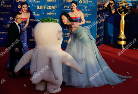 """Xu Chengyi, Bai Baihe Chinese actress Bai Baihe, right, and Director of the movie """"Monster Hunt"""" Xu Chengyi, left, direct the movie character on the red carpet as they attend the closing ceremony of the 5th Beijing International Film Festival in the Huairou district of Beijing"""