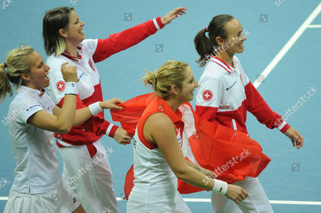 Stock Picture of Timea Bacsinszky, Martina Hingis, Viktorija Golubic, Romina Oprandi CORRECTS TO Romina Oprandi - From left, Switzerland's Viktorija Golubic, Romina Oprandi, Timea Bacsinszky, and Martina Hingis, celebrate their win over Poland in the Fed Cup World Group Playoff tennis match between Poland and Switzerland, in Zielona Gora, Poland
