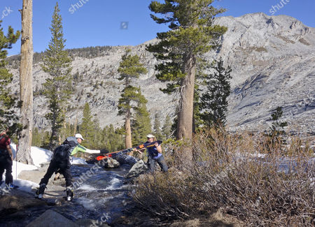 Stock Picture of Dane Shoemaker, left, passes a pair of skis across a creek to Mary Small, right, as they set out toward a peak known as Winter Alta in Sequoia National Park, . The area is typically blanketed in enough snow to ski across the creek, but a paltry snowpack forced skiers to hike their gear on trails, across streams and up rocky slopes to reach the snow. A group of friends have taken this trip through deep powder, braved icy slopes and weathered rain, wind and snow in an annual quest to reach a ski cabin in the wilderness of Sequoia National Park for the past 13 years. The fourth year of the devastating drought that has dried up wells, forced mandatory rationing and jeopardized California crops has also put a burden on backcountry skiers in search of their fix