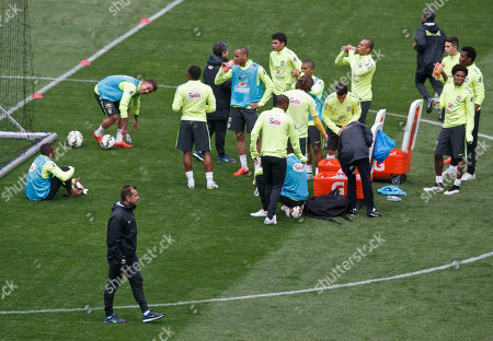 Brazil's soccer team coach Carlos Dunga, foreground watch his team taking a break during a training session of the Brazil national soccer team at Stade de France stadium in Saint Denis, outside Paris, . Brazil will play against France in an International friendly soccer match at Stade de France on Thursday