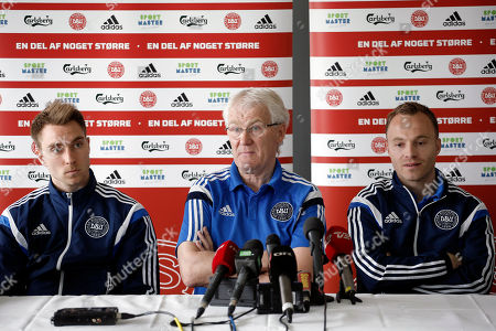Denmark's coach Morten Olsen, center, speaks during a press conference with players Christian Eriksen, left, and Lars Jacobsen in Saint-Etienne, central France, . Denmark will play against France in an friendly soccer match on Sunday