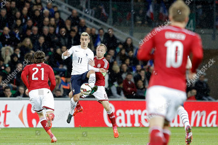 France's Antoine Griezmann, left, challenges for the ball with Denmark's Lars Jacobsen during their international friendly soccer match at Geoffroy Guichard stadium in Saint-Etienne, central France