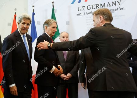 From left: United States Secretary of State John Kerry, British Foreign Secretary Philip Hammond and Canadian Foreign Minister Rob Nicholson arrive for a group photo during a meeting of the G7 Foreign Ministers in Luebeck, northern Germany, . The meeting is being held ahead of the G7 leaders summit in Germany from June 7 to 8, 2015. Person at right is not identified
